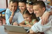 Family sitting with laptop — Stock Photo