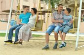Family having fun on  swing — Stock Photo