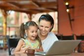 Woman with girl using laptop — Stock Photo