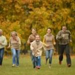 Family running in autumn park — Stock Photo #70973465