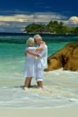 Elderly couple standing on  beach — Stock Photo