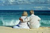Elderly couple sitting on  shore — Stock Photo