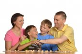 Family of four people playing lotto — Stock Photo