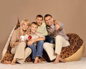 Family sitting on  armchair with tea — Stock fotografie