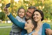 Family taking selfie in park — Stock Photo
