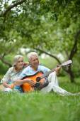 Mature couple with guitar   in park — Stock Photo