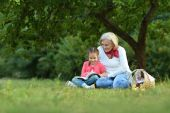 Little  girl with grandmother  and book — Stock Photo