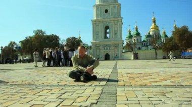 Sad man sits on  sidewalk against church.   Time lapse — Stock Video