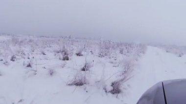 Car goes across  field in  winter. POV FPV view — Wideo stockowe