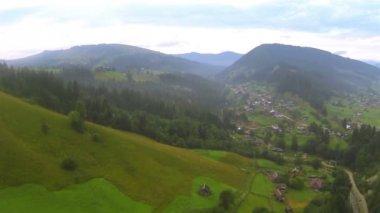 Горные склоны с деревьями и деревня в пасмурный день. Антенна — Стоковое видео