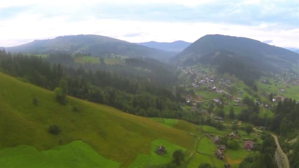Laderas de montaña con árboles y pueblo en día nublado. Aéreo — Vídeo de stock