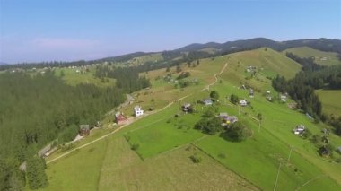 Flight over  hill in mountains with village and wood. Aerial — 图库视频影像