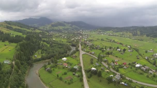 Green valley with settlement in mountains. Aerial  shot — Vidéo