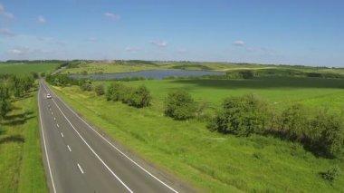 Carro sozinho na estrada. Aerial paisagem com colinas e lago — Vídeo stock