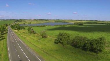 Estrada vazia. Aerial paisagem com colinas e lago — Vídeo stock