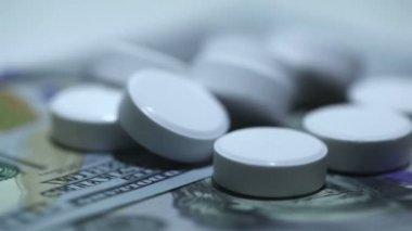 White tablets and money in rotation on  white background. Macro — Stock Video