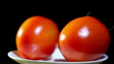 Two tomatoes  turns on  white plate, black background — Stock Video
