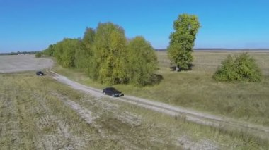 Lonely car on  rural dirt road with shadow of drone. Aerial — Stock Video
