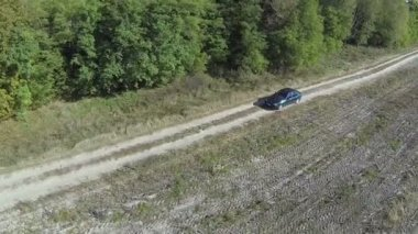 Green car goes on  dirt road in  field. Aerial  top view — Stock Video