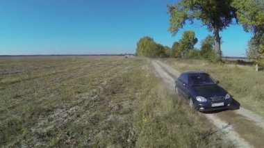 Lonely  green car on  rural dirt road . Aerial  summer day — Stock Video
