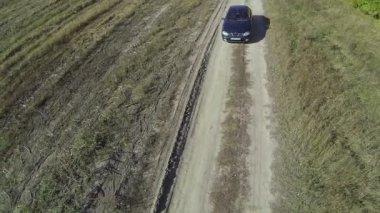 Samotny zielony samochód na wiejskiej drodze brudu. Lotu ptaka widok z góry — Wideo stockowe