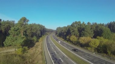 Highway with cars in sunny day and wood. Aerial — Stock Video