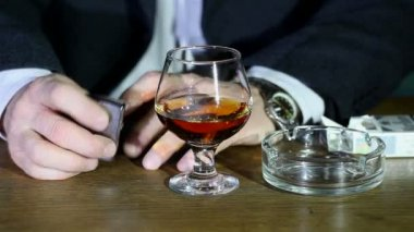 Cognac, lighter and time. Nervous businessman. — Stockvideo