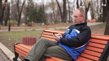 Adult man talking on  mobile in  park — Stockvideo