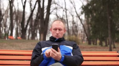 Adult serious  man talking on  mobile in  park. Front view — Стоковое видео
