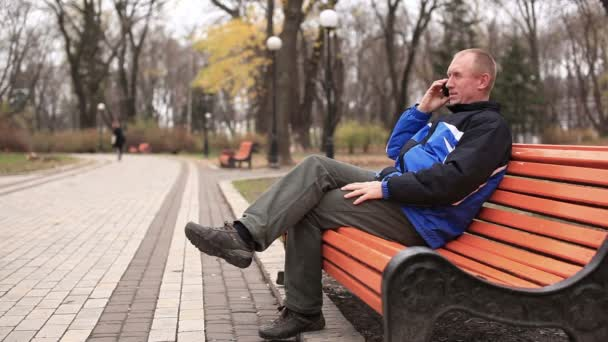 Adult man talking on  mobile and smile in  park — Vidéo