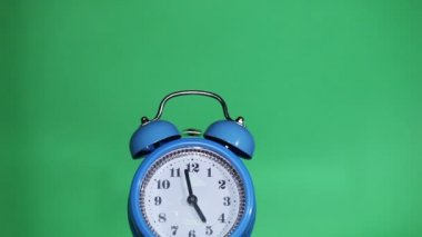 Ringing classical alarm clock ,  green background, five  o'clock — Stock Video