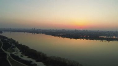 Flight over river  with city  on   red sunset. Aerial shot — Stock Video