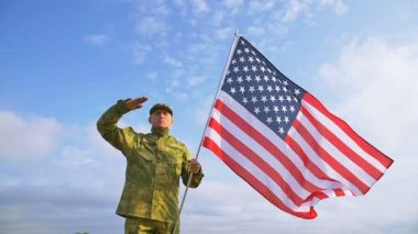 Soldier salute with  American flag against    blue sky. Slow motion scene — Stock Video