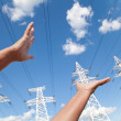 Hands reach for power transmission lines against blue sky — Stock Photo #60442997