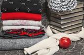Stack of winter clothes and books with silver edge — Stock Photo