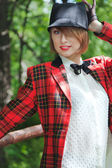 Beautiful young woman in horsewoman suit walks in forest — Stockfoto