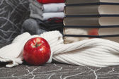 Stack of books with glossy edge and red apple — Stock Photo