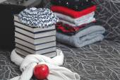 Stack of winter clothes and books with glossy edge — Stockfoto