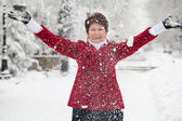 Woman throws up snow on winter snowy street — Stock Photo