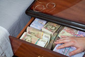 Hand on the money in bedside table — Stock Photo