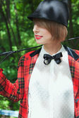 Portrait of beautiful young woman in horsewoman suit in forest — Stock Photo
