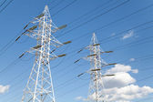 Power transmission lines against blue sky — Stockfoto