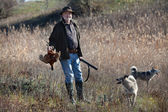 Hunter with a wildfowl and dogs — Stock Photo