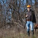 Elderly hunter with wildfowl in orange hat — Stock Photo #62149661