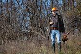 Elderly hunter with wildfowl in orange hat — Stock Photo