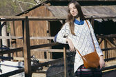 Young beautiful girl stands near the aviary with lamb in city zo — Stock Photo