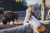 Young beautiful girl stands near the aviary with bison in city z — Stock Photo