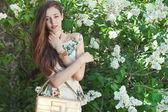 Beautiful young girl model posing near blooming lilacs at spring — Stock Photo