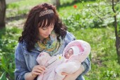 Young mother with newborn baby in outdoors at spring day — Stock Photo