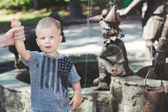 Little boy standing next to fountain in wet t-shirt — Stock Photo